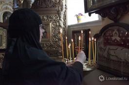 Сестра зажигает свечку в Храме Казанской иконы Божией Матери.